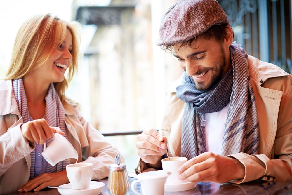 Portrait of affectionate couple in stylish clothes having coffee in cafe
