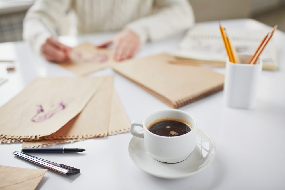 Image of cup of coffee on background of man drawing