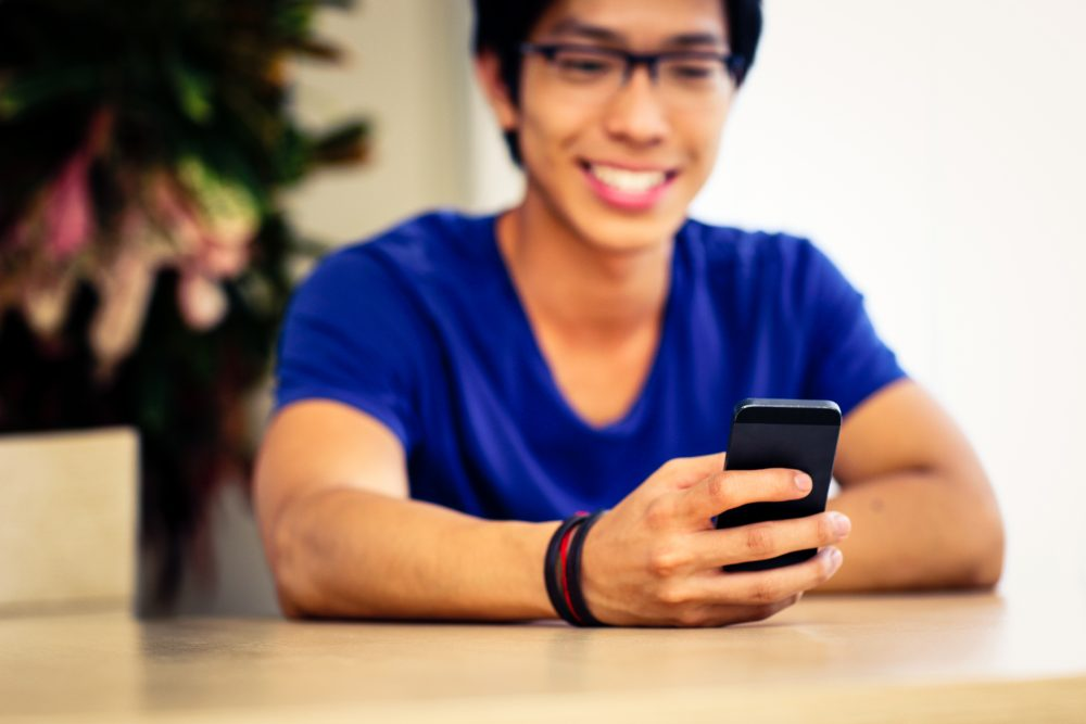 Closeup portrait of a man using smartphone. Focus on smartphone
