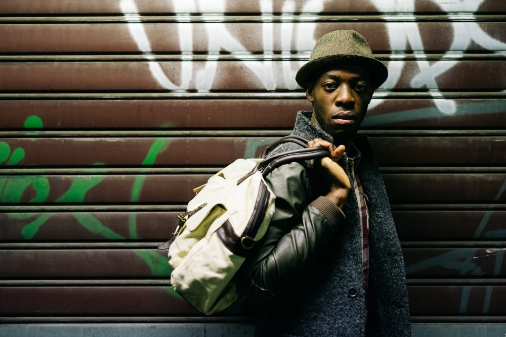 Half length of young handsome afro black man holding a bag, leaning against a rolling shutter, looking in camera, serious - pensive, thoughtful, travel concept