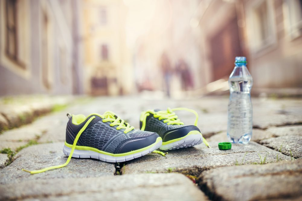 Running shoes and bottle of water left on tiled pavement in old city center