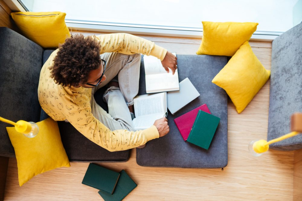 Top view of african young man studying and reading books at home