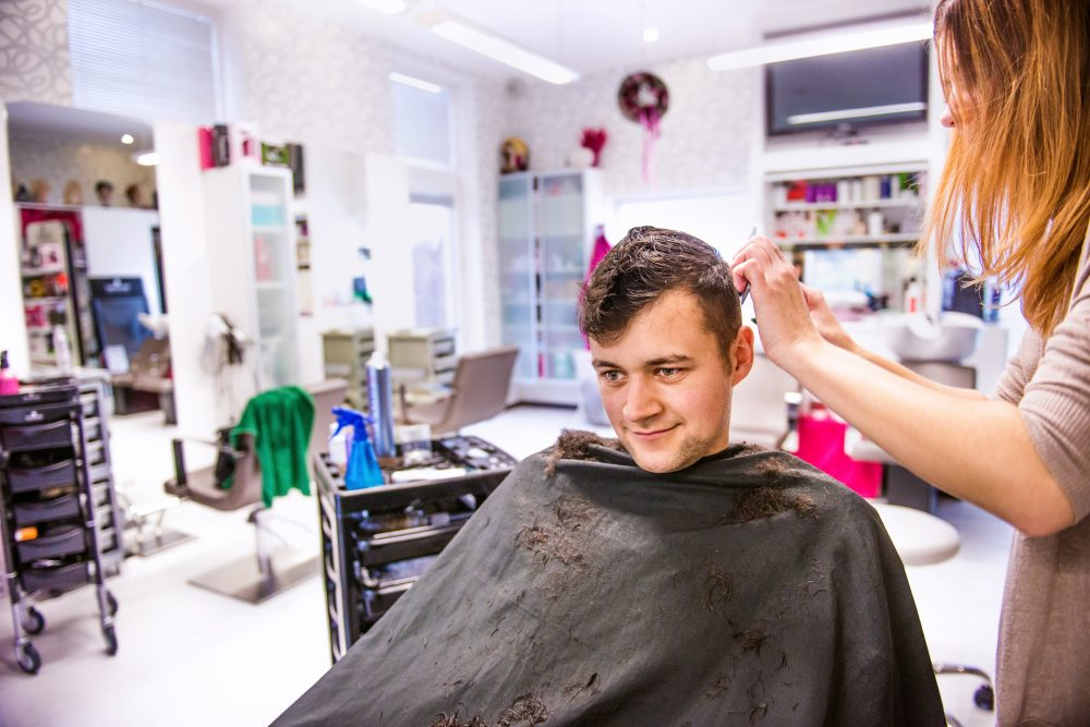 Unrecognizable professional hairdresser cutting hair of her young client, making a new haircut. Barber at work. Man at barbershop.