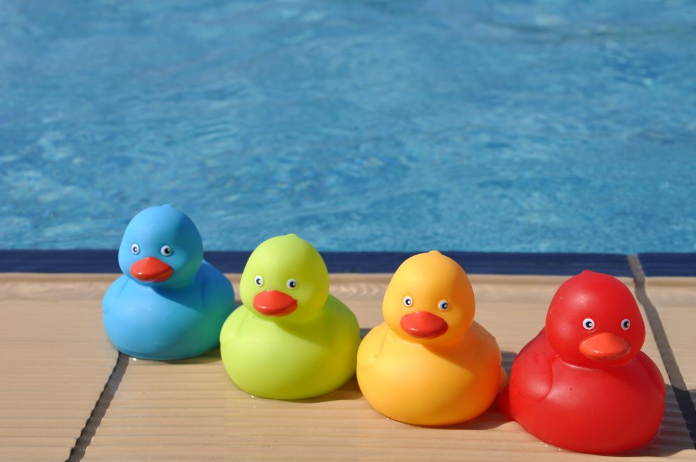 four colorful rubber ducks at the pool side (kids toy)