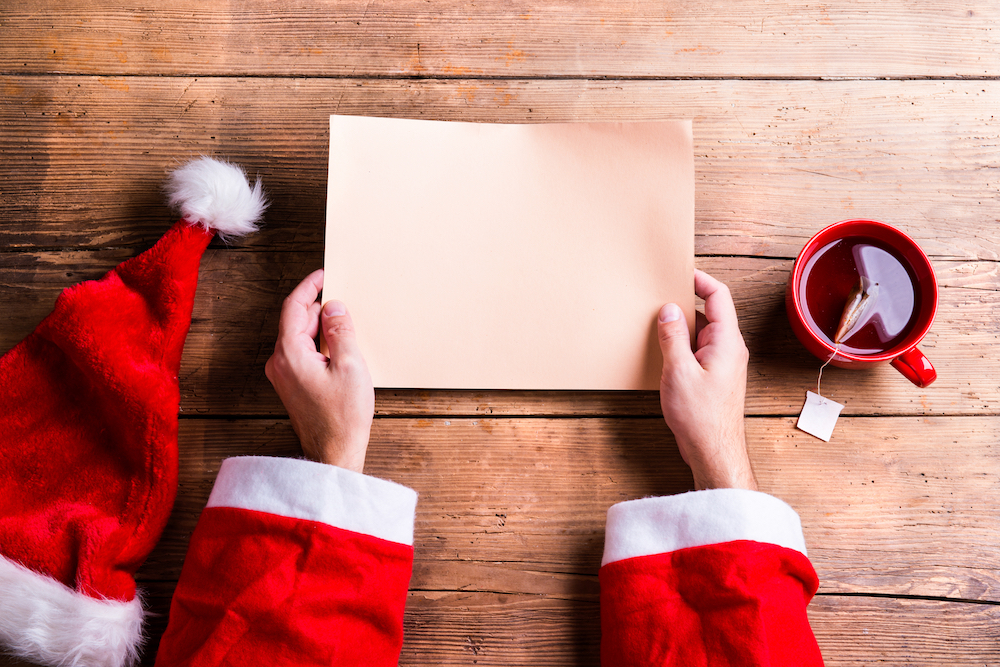 Santa Claus holding an empty wish list in his hands