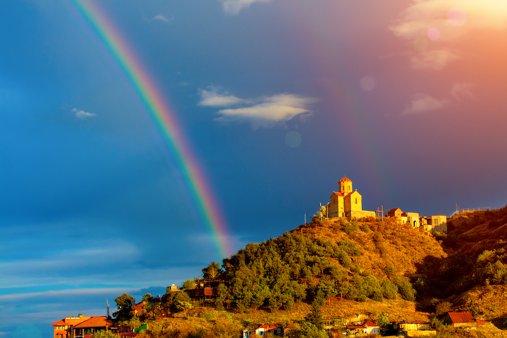 Thabori monastery on a hill with rainbow behind in Tbilisi, Georgia country