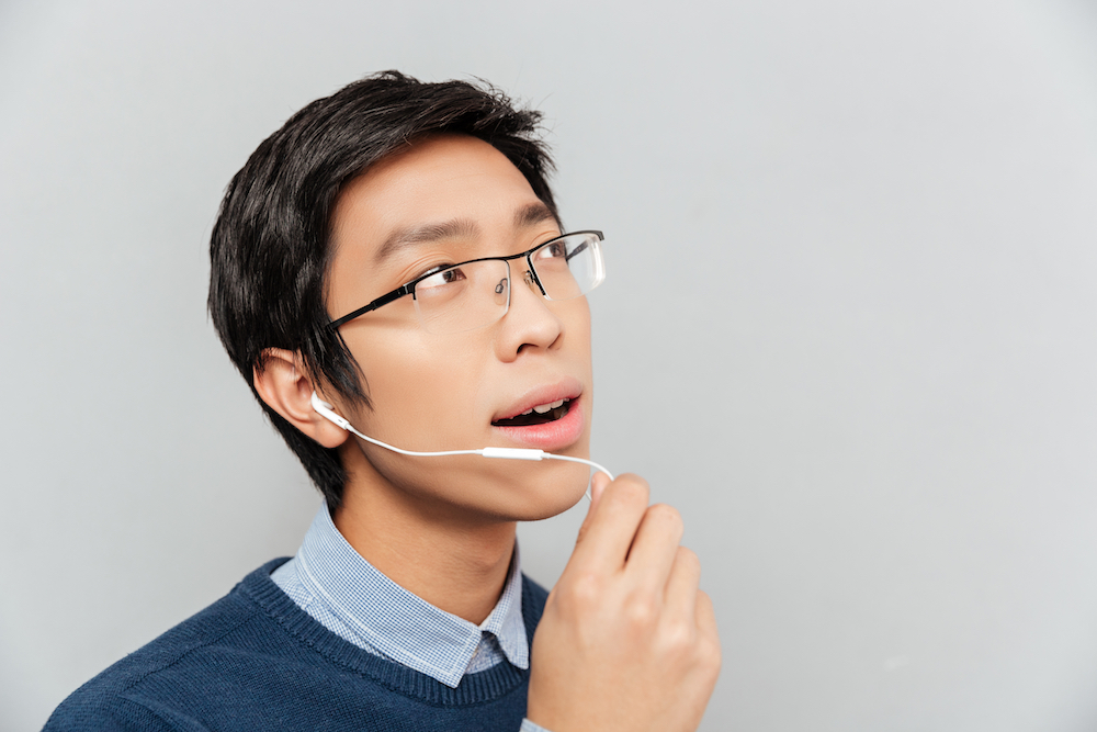 Asian man talking on headphones. with glasses. gray background