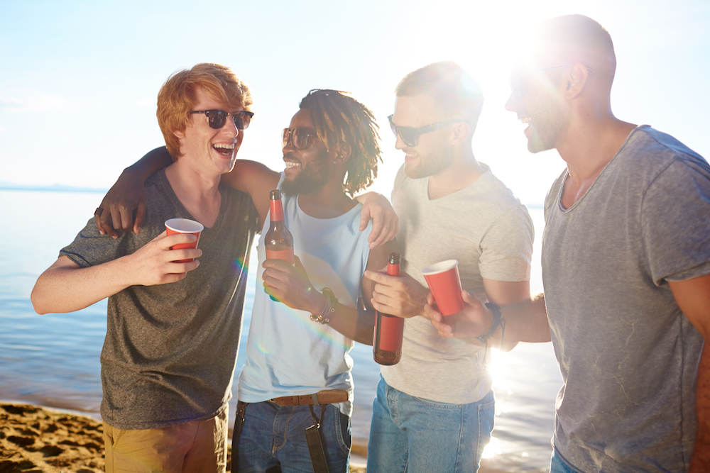 Cheerful buddies enjoying beach party on hot day