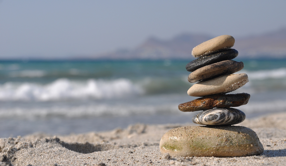 beautiful pebble stack on a sandy beach (sea on the background)
