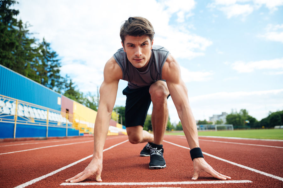 Young concentrated male athlete about to start a sprint and looking at camera